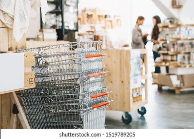 Zero waste food shopping. Metal basket for grocery goods and different reusable glass jars for buying and storage products. Details interior in sustainable plastic free store. Local small business.