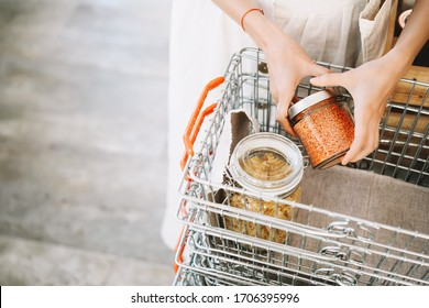Zero waste food shopping. Metal basket with grocery products in reusable glass jars. Woman buying bulk dry goods in sustainable plastic free store. Eco-friendly low waste concept. Minimalist lifestyle