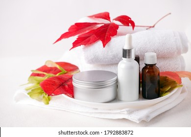 Zero waste Glass cosmetic bottles and metal jar, cream, serum, soap, oil on white table. Autumn bright red leaves, natural organic beauty product. Spa, skin care, bath body treatment. Set of cosmetics