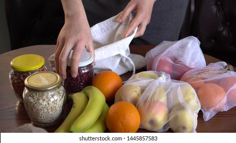 Zero Waste Grocery Shopping. Plastic Free Lifestale. Fabric Shopper Bag. Shop in Bulk. Low waste. Housewife uses reusable glass containers and cloth bags to buy food