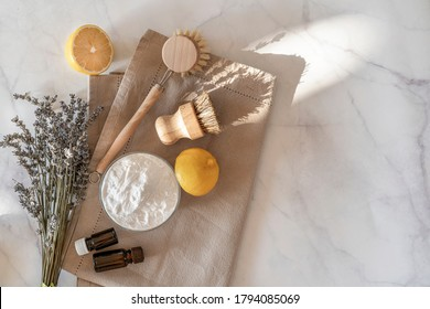 Zero waste kitchen cleaning concept. Eco friendly natural cleaning tools and products, bamboo dish brushes and lemon with baking soda. No plastic, eco-friendly lifestyle. Top view, flat lay.