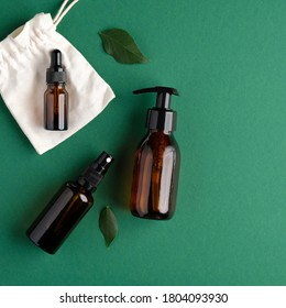 Zero waste organic SPA cosmetics set with green leaves. Top view amber glass bottles on green background. Natural skincare beauty products packaging design.