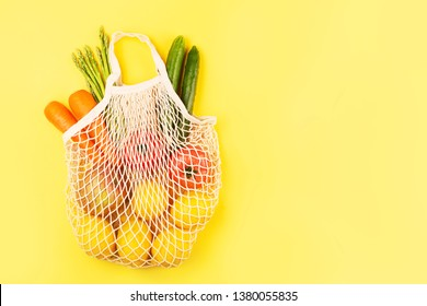 Zero waste and plastic free concept. Grocery shopping with eco bag. Sustainable and eco friendly lifestyle concept. Yellow background. Flat lay, top view. Copy space.