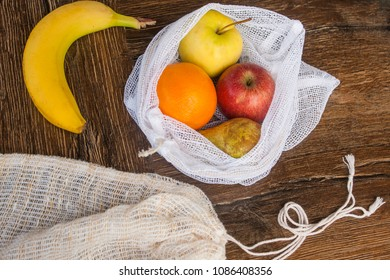 Zero waste, plastic free recycled textile produce bag for carrying fruit (apple, orange, pear and a banana) or vegetables, a wooden surface. Bags are made with a sewing machine out of old curtains.