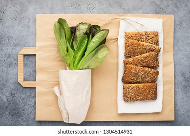 Zero waste shopping. Sheet lettuce, portioned oatmeal bread on an eco bag of paper on a light gray background. Top view.