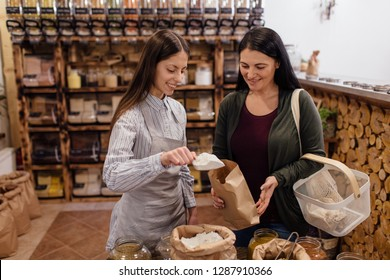 Zero waste shopping - woman buying food at package free grocery store. Helpful shop assistant scooping flour for customer in packaging free shop.