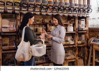 Zero waste shopping - woman buying healthy food at package free grocery store. Helpful shop assistant serving customer in packaging free shop.