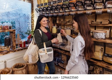 Zero waste shopping - woman buying healthy food in package free store. Cheerful shopkeeper helping customer in packaging free shop.