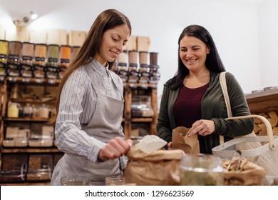 Zero waste shopping - woman buying flour at package free grocery store. Low angle view of friendly shop assistant scooping flour for customer in packaging free shop.