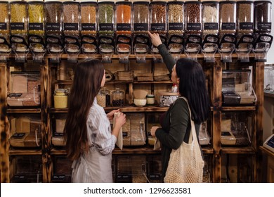 Zero waste shopping - woman buying healthy food in package free store. Shopkeeper helping customer in packaging free shop.