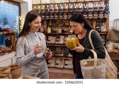 Zero waste shopping - woman smelling fresh spices in jars at package free grocery store. Cheerful shop assistant helping customer in packaging free shop.