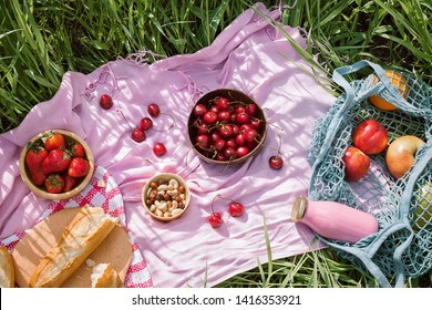 Zero waste summer picnic on the with cherries in the wooden coconut bowls, fresh bread and glass bottle of juice or smoothie on pink blanket, flatlay