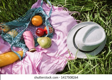 Zero waste summer picnic on the with fresh fruits and bottles of juice or smoothie on pink blanket, flatlay
