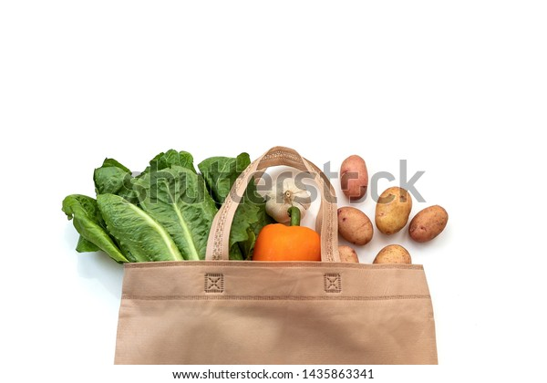 Zero waste use less plastic concept / Fresh vegetables organic in eco cotton fabric bags on wooden table - white tote canvas cloth bag from market free plastic shopping