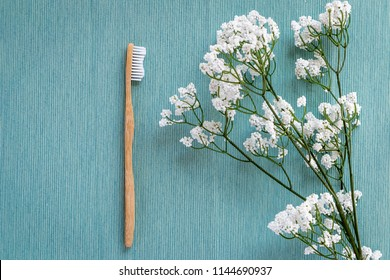 Zero-waste, biodegradable bamboo toothbrush on a blue canvas background with a white flower on the side.