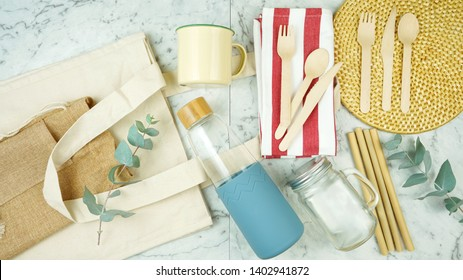 Zero-waste, plastic-free tableware flatlay overhead with bamboo and natural fibers to replace single use plastic products.