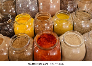 Zero-waste shopping - spices in jars. Composition of colorful assorted spices and herbs in glass jars in packaging free shop.