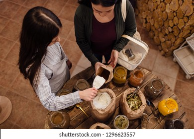 Zero-waste shopping - woman buying fresh herbs and spices at package free grocery store. High angle view of shop assistant scooping flour for customer in packaging free shop.