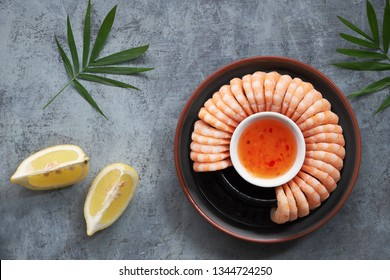 Zesty lemon and garlic prawns served on a dark plate with lemons and sweet chili sauce, flat lay on dark background