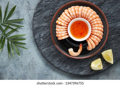 Zesty lemon and garlic prawns served on a dark plate with lemons and sweet chili sauce, flat lay on dark stone serving board