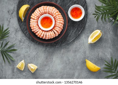Zesty lemon and garlic prawns served on a dark plate with lemons and sweet chili sauce, flat lay on greyk background