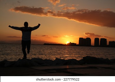 """""""Zeybek"""" dance in Izmir.  Turkish traditional dance. Folklore from Turkey. Sunset dance. Silhouette of people by the sea at sunset"""