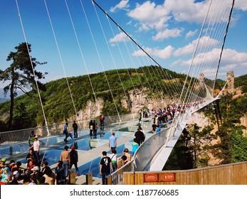 Zhangjiajie,China April 2,2018 : Zhangjiajie's National Forest Park, People Visiting Zhangjiajie Grand Canyon Skywalk Glass Bridge with Beautiful Blue Sky and Mountain Background.