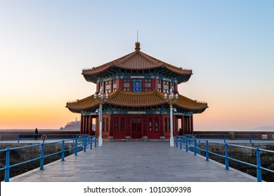 "Zhanqiao pier at sunrise, Qingdao, Shandong, China. The name ""Huilan Pavilion"" is engraved above the entrance door."