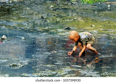 ZHAOXING DONG, CHINA - JUNE 21, 2012: Chinese boy child playing in black stagnant, muddy water in traditional Mioa minority village.