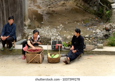 ZHAOXING DONG, CHINA - JUNE 21, 2012: Chinese Miao minority women selling fresh raspberries fruitsand vegetables in the street.