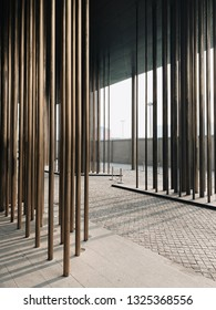 Zhengzhou/China-February 21,2019 : Light passing through the brass metal columns casting shadow of a drop-off canopy at Le Meridien Hotel in Zhengzhou, designed by Neri&Hu.