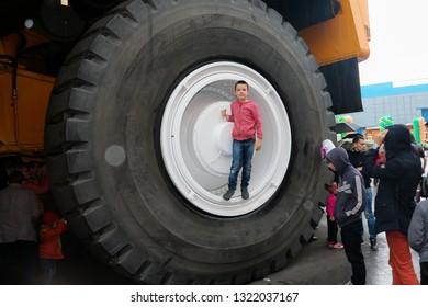 Zhodzina, Belarus - September 29 2018: annual exhibition of Belaz in Belarus, Zhodino, Minsk region. Belaz is a Belarusian manufacturer of haulage and earthmoving equipment. The boy got on the wheel.