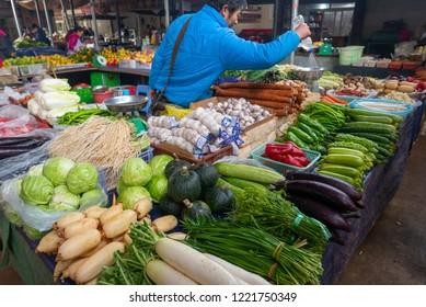 ZHONGDAN, XIANGGELILA, SHANGRI LA, DEQEN, YUNNAN - CIRCA OCTOBER 2017 : Unidentified Chinese man sprays water to keep the vegetable fresh in Zhongdan wet market, Shangri-La, Yunnan, China.