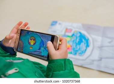 Zhongshan, China - February 7, 2018: kid playing Augmented Reality popup paintings of a color filled igloo and polar bear via mobile. AR and VR games become more and more popular.