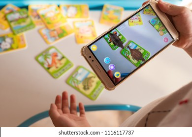 Zhongshan,China-April 22,2018:kid playing Augmented Reality popup of tyrannosaurus and ankylosaurus via mobile. AR and VR games become more and more popular.