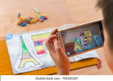 Zhongshan,China-August 29, 2017:kid playing Augmented Reality popup paintings of the filled Arch of Triumph & Eiffel Tower via mobile. AR and VR games become more and more popular.