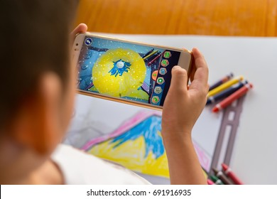 Zhongshan,China-August 8, 2017:kid playing Augmented Reality popup paintings of a filled mountain via mobile. AR and VR games become more and more popular.