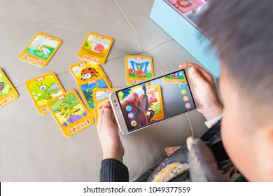 Zhongshan,China-December 30, 2017:kid playing Augmented Reality popup of scorpion via mobile. AR and VR games become more and more popular.