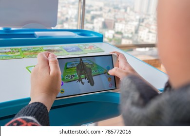 Zhongshan,China-December 30, 2017:kid playing Augmented Reality popup of Spinosaurus via mobile. AR and VR games become more and more popular.