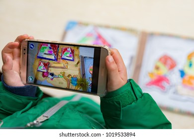 Zhongshan,China-February 7, 2018:kid playing Augmented Reality popup paintings of a color filled pyramid via mobile. AR and VR games become more and more popular.