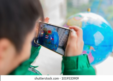 Zhongshan,China-February 7, 2018:kid playing Augmented Reality popup globe with flags via mobile. AR and VR games become more and more popular.