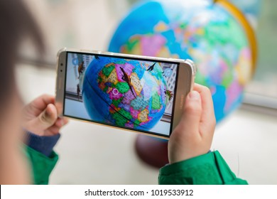 Zhongshan,China-February 7, 2018:kid playing Augmented Reality popup globe with dinosaurs via mobile. AR and VR games become more and more popular.