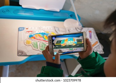 Zhongshan,China-February 8, 2018:kid playing Augmented Reality popup paintings of a color filled car and road via mobile. AR and VR games become more and more popular.