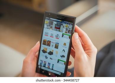 Zhongshan,China-November 27, 2015:young women shopping through mobile on Amazon on Black Friday.More & more Chinese people shopping through internet internationally.