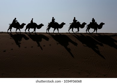 Zhongwei city, China - Sep 30, 2008: Tourists riding camels in a row in the Shapotou sand dune of Tengger Desert, Zhongwei city, China - Sep 30, 2008.