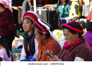Zhoucheng village, Yunnan, China - November, 2018. Women from various ethnic minorities of Yunnan with their traditional clothes in the market of Zhoucheng village, Yunnan, China