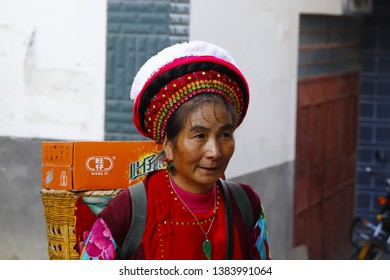 Zhoucheng village, Yunnan, China - November, 2018. A woman of an ethnic minority of Yunnan with her traditional clothes in the market of Zhoucheng village, Dali, Yunnan, China
