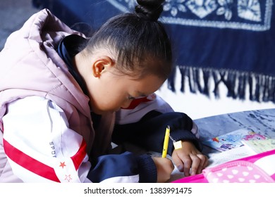 Zhoucheng village, Yunnan, China - November, 2018. A little girl doing school lessons in Zhoucheng village, Dali, Yunnan, China