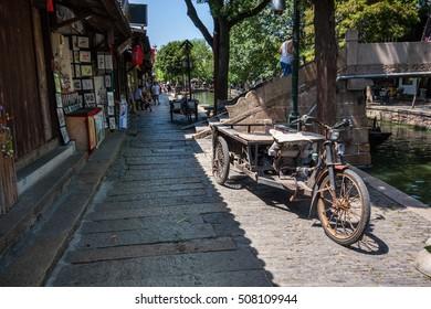 ZHUJIAJIAO, CHINA - AUGUST 30, 2016: Rusty three wheeled freight electric bike parked on canal embankment of ancient water town in Zhujiajiao, China, on August 30, 2016.