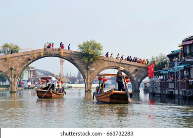 ZHUJIAJIAO, CHINA - NOVEMBER 10, 2014: Sightseeing boats take tourists under the famous Fangsheng Bridge in ancient water town of Zhujiajiao located in the Qingpu District of Shanghai.